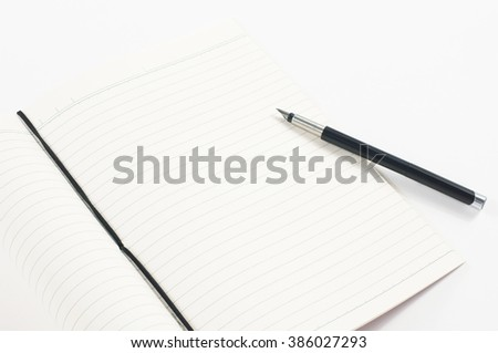 A fountain pen on an opened blank notebook, on white background.