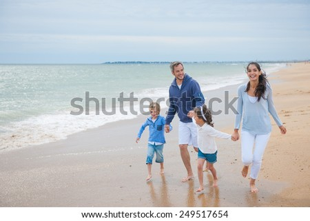 a four people family is playing at the beach in casual wear, the parents and their children are laughing and running in the sea waves - stock photo