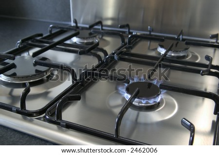 A four ring brushed steel gas hob with focus on the burning ring, - stock photo