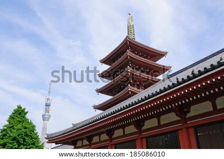 A four story pagoda set against a blue sky. - stock photo