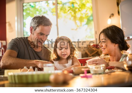 A four years old blonde girl is cooking small cakes with her mother and grey haired father in a luminous kitchen. They are working on a pastry with water and flour on a table full of ingredients - stock photo