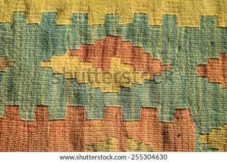 A fragment of a beautiful and coloured traditional handmade turkish carpet with geometrical shapes and green, yellow, red colors - stock photo