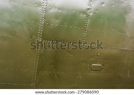 A fragment of the old airplane close-up. Abstract military green metal plates background texture with seams and rivets