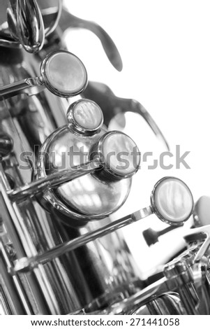A fragment of the valve of the saxophone in black and white