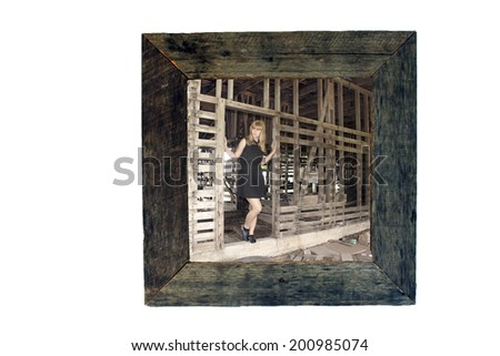 A frame made with real aged and weathered wood containing a photograph of a pretty girl in an old barn.  Generous copyspace. - stock photo