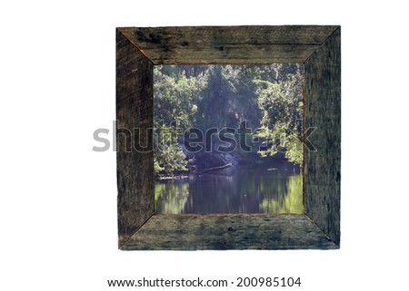 A frame made with real aged and weathered wood containing an outdoor scenic photograph.  Generous copyspace. - stock photo