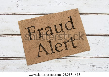 A Fraud Alert Warning Card, A brown card with words Fraud Alert over a distressed wood background  - stock photo