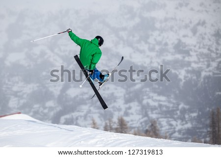 A free-ride ski jumper, with skis crossed against a mountains