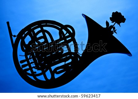 A French horn and rose flower in silhouette isolated against a blue background. - stock photo
