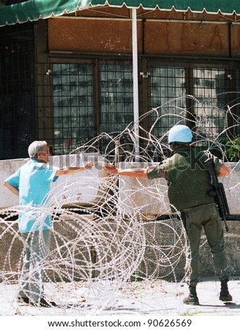 A French peacekeeper, in Bosnia with the United Nation's UNPROFOR, gives a local man a cigarette outside his barracks in Sarajevo, Bosnia, on Wednesday, Thursday, April 22, 1993.
