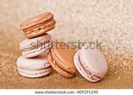 A french sweet delicacy, macaroons vanilla and caramel on gold background.