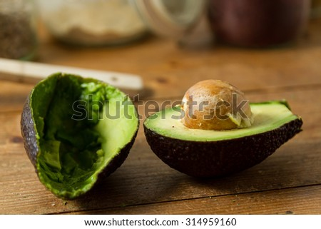 A fresh avocado cut in half, against a wooden background. - stock photo