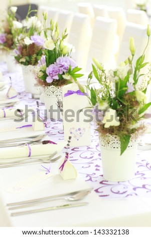 A fresh bouquet of flowers lies on a white wedding reception table setting. Shallow focus.
