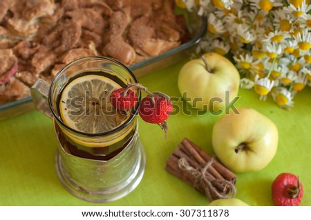 A fresh bright composition with a cup of strong black tea with a lemon slice, an apple pie, a bouquet of chamomiles, cinnamon sticks, ripe apples and mature hips on a light green linen surface
