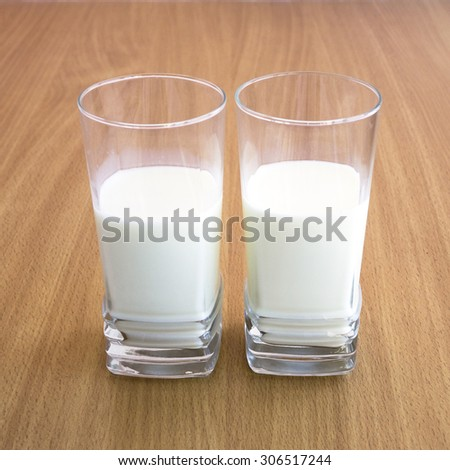 A fresh cold milk in high transparent glass. Let us eat cake with milk.  - stock photo