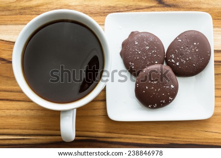 a fresh cup of coffee with salted caramels with a teak wood background