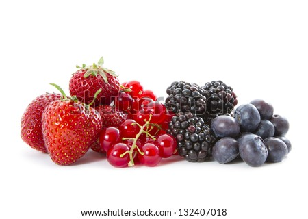 A fresh heap of organic strawberries, blueberries, currants and blackberries on white background.