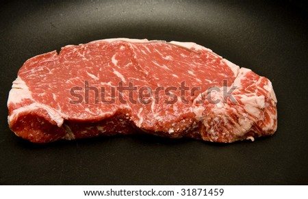 A fresh, juicy, steak being cooked in a hot skillet
