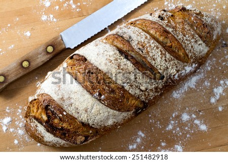 A fresh loaf of cranberry walnut bread and a bread knife - stock photo