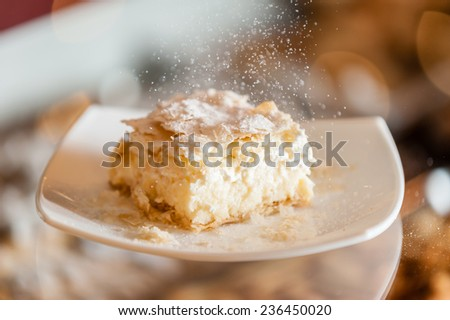 A fresh piece of coconut vanilla cream cake on a white plate