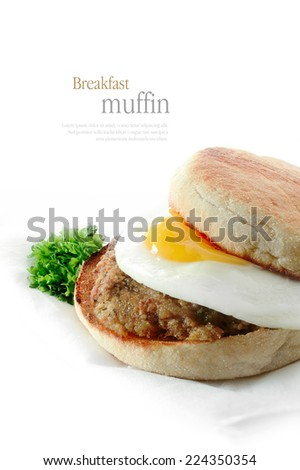 A fresh pork sausage patty and fried egg breakfast muffin against a white background. Copy space. - stock photo
