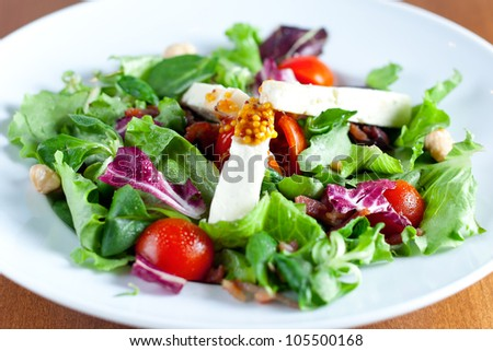 A fresh salad made of mixed lettuces, cherry tomatoes, nuts, goat cheese and dijon mustard on top. Shallow depth of field on the mustard topping.