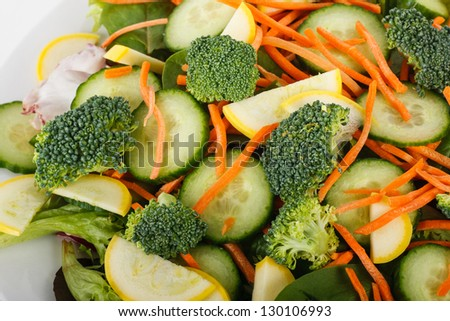 A fresh salad of fresh cucumber, squash, broccoli, carrots and lettuce in a white bowl
