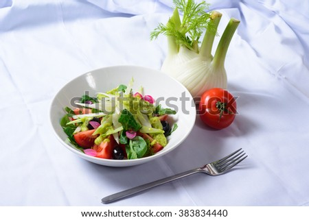 A fresh salad of tomatoes and greens on a dark background