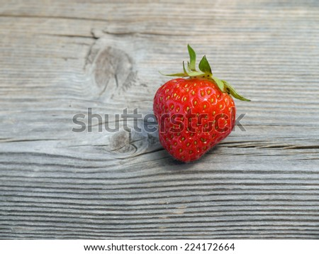 a fresh strawberry on a wooden board - stock photo