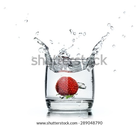 A fresh strawberry splashing water in a glass on white background - stock photo