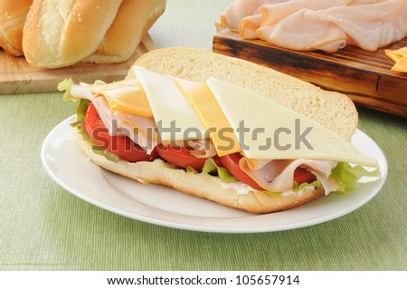 A fresh submarine sandwich with the ingredients in the background