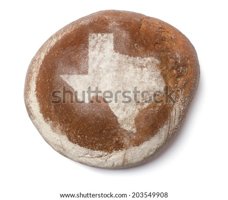 A freshly baked loaf of bread covered with rye flour in the shape of Texas.(series) - stock photo