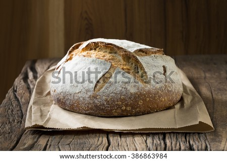 A freshly baked rustic, sourdough loaf of bread on an old wooden table.