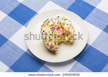 A freshly bitten, delicious icing coated cake donut with sweet sprinkles on a classic, checkered diner tablecloth  - stock photo