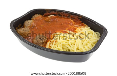 A freshly cooked spaghetti and meatball TV dinner in the black plastic tray on a white background. - stock photo