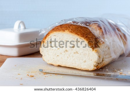 A freshly cut tiger bloomer bread loaf on a white chopping board against a blue background - stock photo