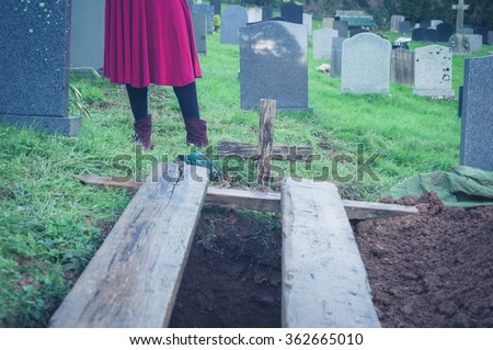 A freshly dug open grave in a cemetery with a woman standing in the background - stock photo
