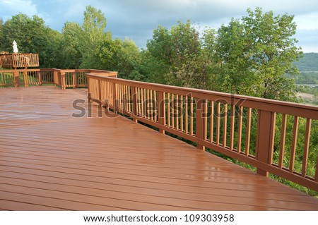 A freshly painted and stained wood deck with railing on a summer afternoon after a rain shower. - stock photo