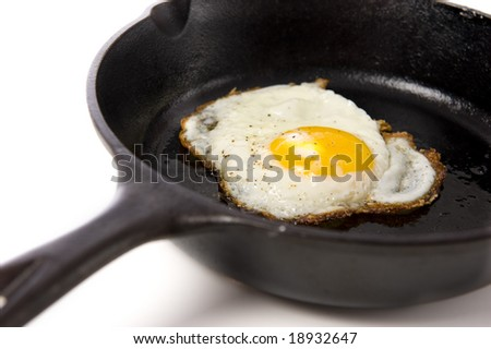 A fried egg in a black iron skillet on a white background, food, nourishment concept