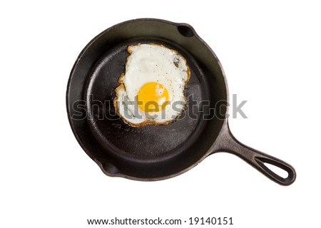A fried egg in a black iron skillet on a white background, food, nourishment concept - stock photo
