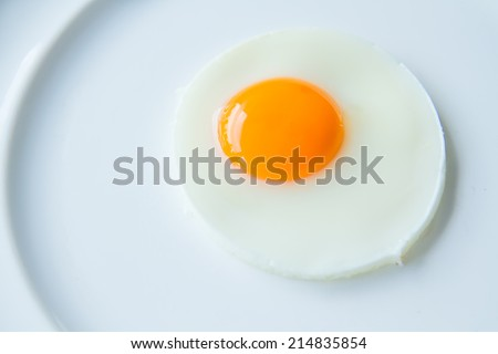 A fried egg on white dish - stock photo