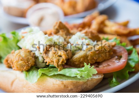 A fried oyster po-boy sandwich with cole slaw, french fries, and remoulade sauce - stock photo