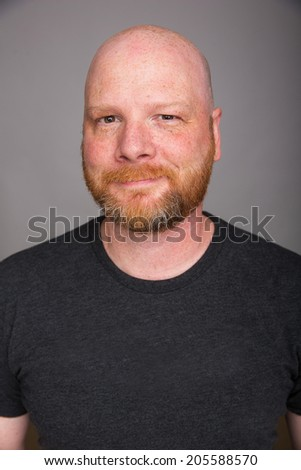 A friendly looking bald man with a red beard - stock photo