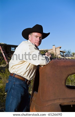 A friendly looking man in a black cowboy hat leaning on an old, long abandoned car. - stock photo