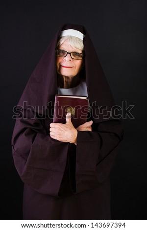 A friendly nun holding a bible - stock photo