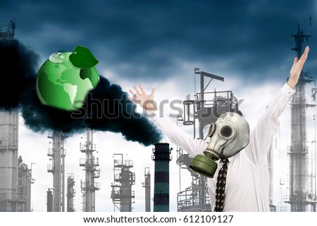 A frightened engineer ecologist in a gas mask against the background of smoking industrial pipes throwing out toxic gases into the atmosphere