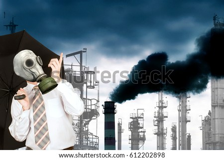 A frightened engineer ecologist with umbrella in a gas mask against the background of smoking industrial pipes throwing out toxic gases into the atmosphere