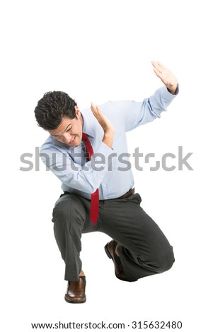 A frightened hispanic male office worker in business clothes, head down, crouching putting up hands shielding in self defense under attack. Workplace violence isolated on white - stock photo