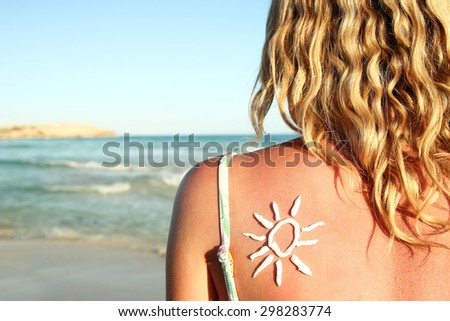 a from sun cream on the female back on the seaside - stock photo