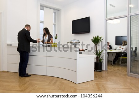 A front desk lady doing her job very well and cheerfully while she's consulting a customer. The black space on the TV-screen could be used for any logos, some label signs or any graphic additions. - stock photo